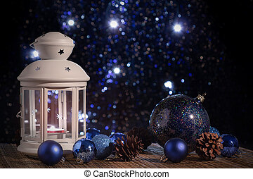 White lantern with a burning candle on the background of the Christmas tree with lights. Beautiful christmas or new year background