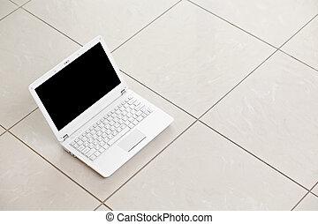 White laptop on bright tiled floor. - White laptop on bright...