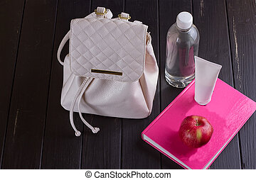 White leather backpack, pink book, bottle of water on a...