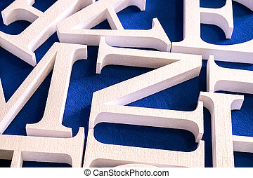 white letters cut out of foam without painting on a blue ...