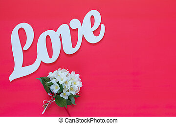 White letters forming word LOVE written with  jasmine flower bouquet