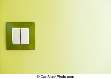 White light switch on a green wall