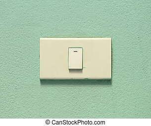 light switch on green cement wall
