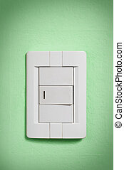 White light switch on green wall.