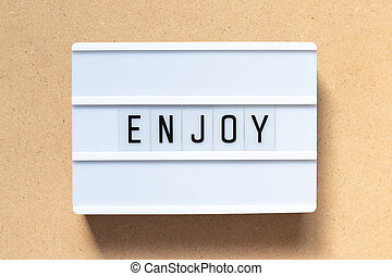 White lightbox with word enjoy on wood background