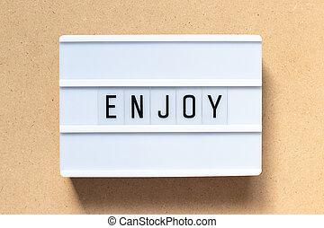 White lightbox with word enjoy on wood background