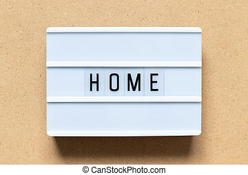White lightbox with word home on wood background