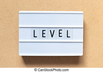 White lightbox with word level on wood background