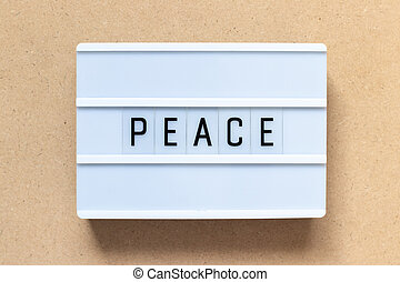 White lightbox with word peace on wood background
