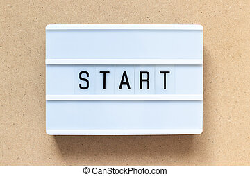 White lightbox with word start on wood background
