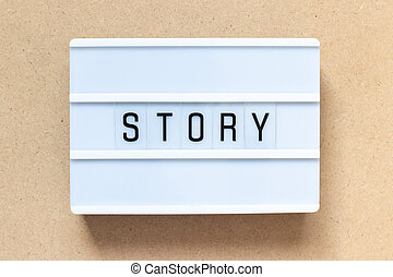 White lightbox with word story on wood background