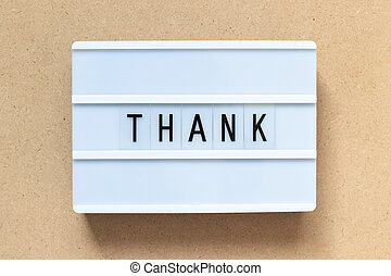 White lightbox with word thank on wood background
