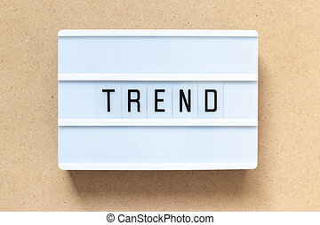 White lightbox with word trend on wood background