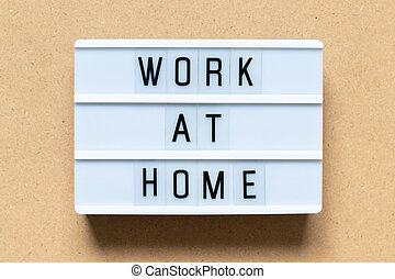 White lightbox with word work at home on wood background