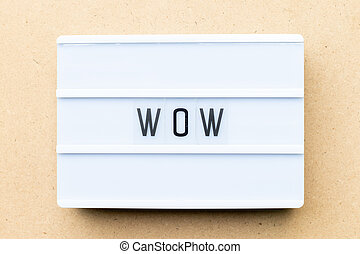 White lightbox with word wow on wood background