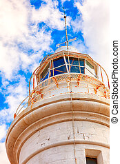 White lighthouse against blue sky with clouds.