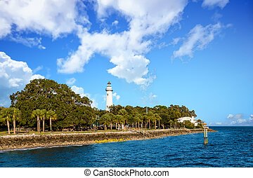 White Lighthouse Rising from Coastal Park - Trees along a ...