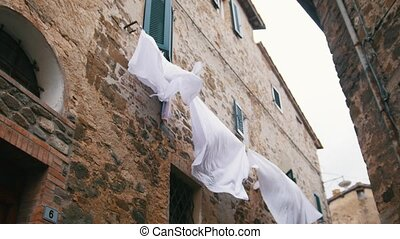 White linen hanging on the dryer under the windows. Mid shot
