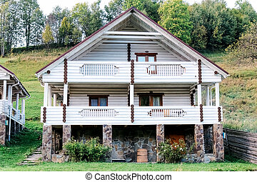 White log house chalet on mountain hills. Beautiful wooden two story cottage house in summer on side of mountain. Exterior of house in mountain village.