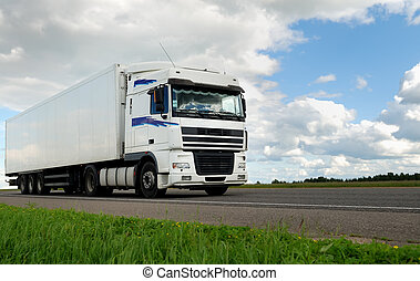 white lorry with white trailer on the highway over blue...