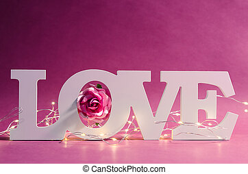 White love text wood and led light with pink rose on wooden background..