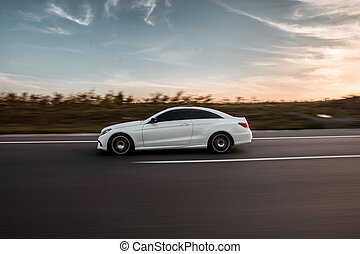 White luxury sedan car driving on the road, profile view