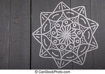 White mandala on dark wooden background