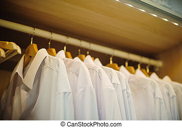 white mans shirts on hangers in store