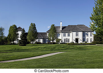 White mansion with cedar shake roof in suburbs