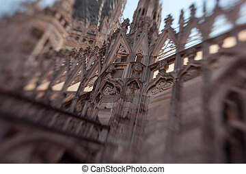 White marble construction on the roof of famous Cathedral Duomo di Milano, piazza in Milan, Italy. Blur and movement