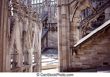 White marble construction on the roof of famous Cathedral Duomo di Milano, piazza in Milan, Italy. Sunny day