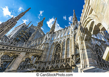 White marble statues on the roof of famous Cathedral Duomo di Milano in Italy