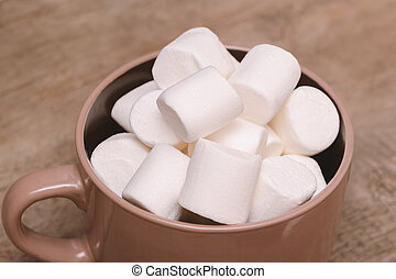 White marshmallow in big cup on wooden background.