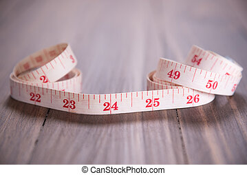 white measuring tape on wood background focus on 24 inch