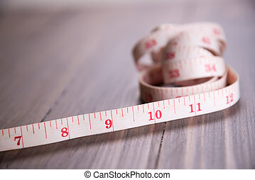 white measuring tape on wood background focus on 9 inch long
