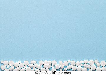 White Medical Pills on Blue Background