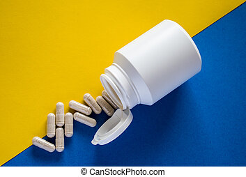 White medical pills with pill box on yellow and blue background