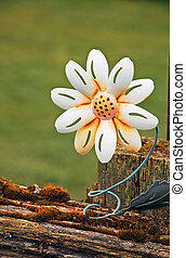 White metal flower on fence