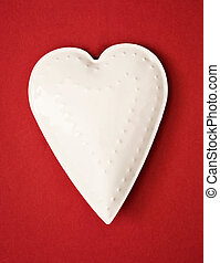 White metal heart on the red background