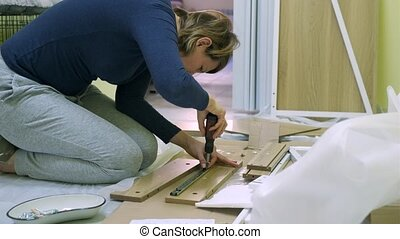 White middle age woman is assembling furniture alone