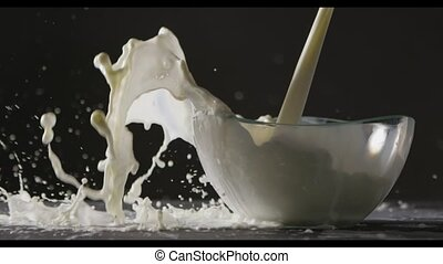 White milk is poured into a glass bowl on a black...