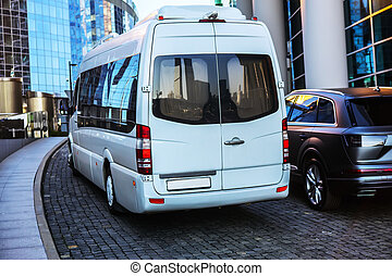 White mini bus moves down the street in the center of the ...