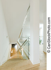 White minimalist staircase with glass balustrade in modern...