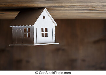 White model of a house staning on a triangle roof upside down  on a brown wooden background
