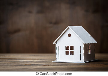 White model of a house with triangle roof on a brown wooden background.
