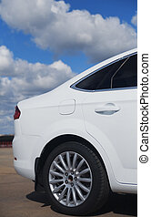 white modern car against the blue sky with clouds