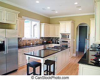 A modern kitchen with white cabinets and black granite countertops. Wine bottles and stainless steel appliances are visible
