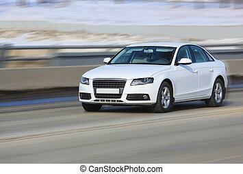 car moves on the road in the winter - white modern the car...