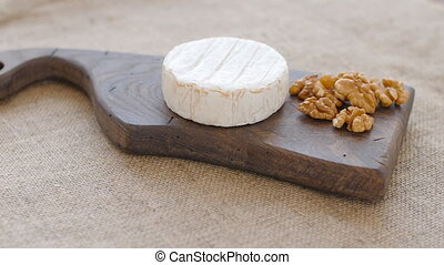 White mold cheese and nuts rotate on a wooden cutting board