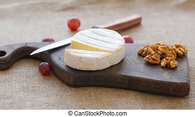 White mold cheese rotate on a wooden cutting board - White...
